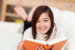 Mujer asiática sonriente que goza de un buen libro Foto de archivo libre de regalías