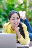 Mujer asiática sonriente que usa el ordenador portátil con los auriculares y el retrete Foto de archivo