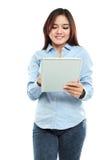 Mujer asiática sonriente que usa la tableta Imagen de archivo libre de regalías