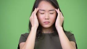 Mujer asiática subrayada jóvenes que tiene dolor de cabeza