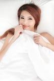 Mujer asiática tímida sonriente debajo de un edredón Fotografía de archivo