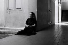 Mujer asiática triste en ropa negra en el edificio viejo Imagen de archivo