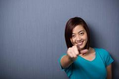 Mujer asiática vivaz que señala en la cámara Foto de archivo