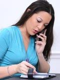 Mujer Asiático-Americana con el teléfono celular y la agenda Foto de archivo
