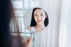 Mujer asi?tica de la belleza joven que mira la cara clara del control del espejo imagen de archivo libre de regalías