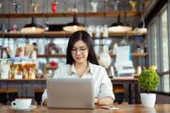 Mujer asi?tica del Freelancer feliz que trabaja usando el ordenador port?til digital imagen de archivo libre de regalías