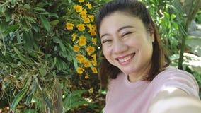 Mujer asi?tica feliz tomar una foto con la flor hermosa de la orqu?dea en el jard?n almacen de video