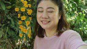 Mujer asi?tica feliz tomar una foto con la flor hermosa de la orqu?dea en el jard?n almacen de metraje de vídeo
