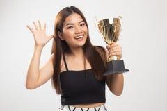 Mujer asi?tica joven acertada que sostiene un trofeo foto de archivo libre de regalías