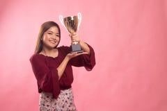 Mujer asi?tica joven acertada que sostiene un trofeo fotografía de archivo