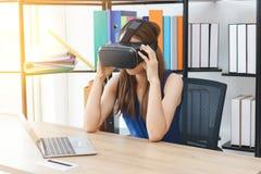Mujer asi?tica joven relajada que lleva los vidrios virtuales de la realidad de VR en lugar de trabajo en oficina fotografía de archivo libre de regalías