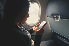 Mujer asi?tica tur?stica que se sienta cerca de ventana del aeroplano y que usa el tel?fono elegante durante vuelo fotos de archivo libres de regalías