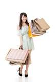 Mujer asiática atractiva que sostiene bolsos de compras Imagen de archivo libre de regalías