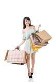 Mujer asiática atractiva que sostiene bolsos de compras Imágenes de archivo libres de regalías