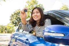 Mujer asiática del conductor de coche que sonríe mostrando nuevas llaves del coche Fotos de archivo libres de regalías