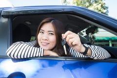 Mujer asiática del conductor de coche que sonríe mostrando nuevas llaves del coche Fotografía de archivo libre de regalías