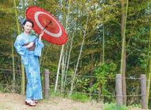 Mujer asiática del kimono con la arboleda de bambú Fotografía de archivo
