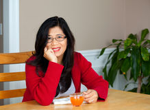 Mujer asiática en años 40 tempranos que se sientan en la tabla con la bebida Imágenes de archivo libres de regalías