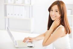 Mujer asiática joven feliz que usa un ordenador portátil Fotos de archivo