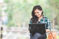 Mujer asiática joven que usa el ordenador portátil mientras que se sienta en el parque Fotos de archivo