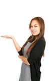 Mujer asiática plana de la mano que exhibe mirando mitad Imagen de archivo libre de regalías