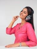 Mujer asiática que desgasta un auricular y que escucha m Imagenes de archivo