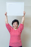 Mujer asiática que lleva a cabo el marco blanco vacío en el tiro del estudio, SP Foto de archivo