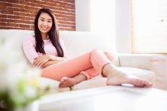 Mujer asiática que se relaja en el sofá Fotos de archivo