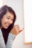 Mujer asiática que se relaja en el sofá con café Imágenes de archivo libres de regalías
