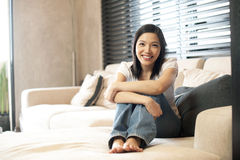 Mujer asiática que se sienta en el sofá con las almohadillas Fotografía de archivo