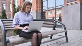 Mujer asombrosa que mecanografía en el ordenador portátil que se sienta fuera de oficina almacen de video