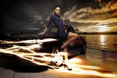 Mujer asombrosa que presenta al lado de su coche, fondo fantástico de la belleza del paisaje Foto de archivo