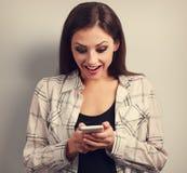 Mujer asombrosamente feliz que mira en teléfono móvil y que lee el SMS w Fotos de archivo