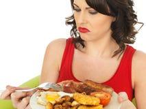 Mujer asqueada joven que come un desayuno inglés lleno Imágenes de archivo libres de regalías