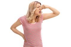 Mujer asqueada que huele algo malo Imágenes de archivo libres de regalías
