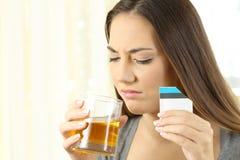 Mujer asqueada que toma una medicina con mún gusto Foto de archivo