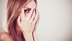 Mujer asustada asustada que mira a escondidas a través de sus fingeres Fotos de archivo libres de regalías