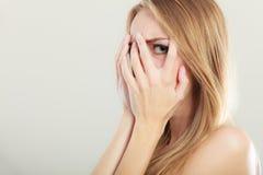 Mujer asustada asustada que mira a escondidas a través de sus fingeres Imágenes de archivo libres de regalías