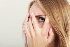 Mujer asustada asustada que mira a escondidas a través de sus fingeres Foto de archivo libre de regalías