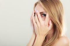 Mujer asustada asustada que mira a escondidas a través de sus fingeres Imagen de archivo