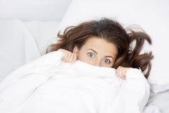 Mujer asustada en cama Imagenes de archivo