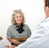 Mujer asustada preocupante que habla con su doctor foto de archivo libre de regalías