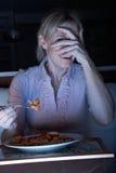 Mujer asustada que disfruta de la comida que ve la TV Imagen de archivo libre de regalías
