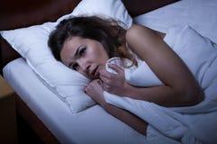 Mujer asustada que intenta dormir Imagen de archivo libre de regalías