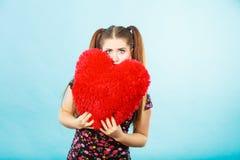Mujer asustada que sostiene la almohada en forma de corazón Fotos de archivo libres de regalías