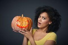 Mujer asustada que sostiene la calabaza de Halloween Imagen de archivo