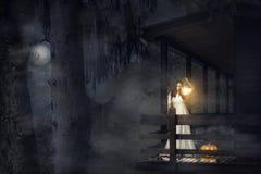 Mujer asustadiza en el vestido blanco en un bosque oscuro Fotos de archivo