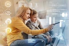 Mujer atenta que sostiene una aguja mientras que muestra un nuevo programa a su hijo imagen de archivo