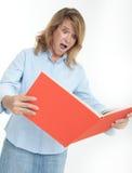 Mujer aterrada que examina un libro Foto de archivo