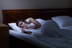 Mujer aterrorizada que miente en cama Foto de archivo libre de regalías